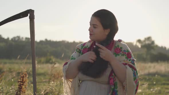 Thumbnail for Beautiful Overweight Woman with a Scythe Braiding Her Hair in Sunlight on the Green Summer Field