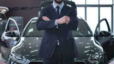 Young Successful Unrecognizable Caucasian Man in Suit Standing in Dealership in Front of New Black