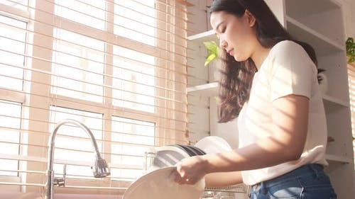 Asia lady washing dishes while doing cleaning in the kitchen at house.