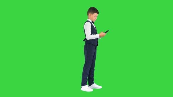 Lächelnder Junge in einem weißen Hemd Fliege und Weste SMS auf dem Telefon auf einem Green Screen Chroma Key