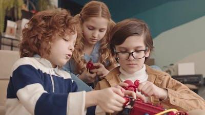 Caucasian School Kids Building Robot Together