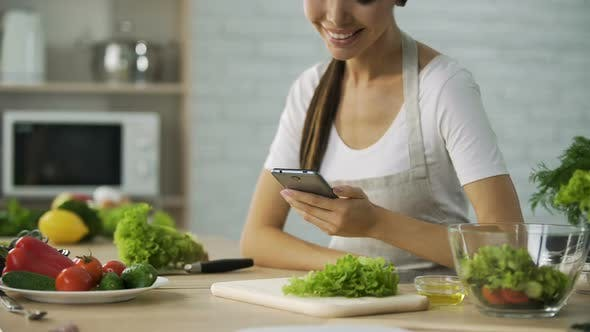 Cover Image for Smiling Asian girl watching video recipe on smartphone before cooking dinner