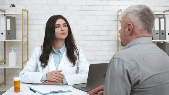 Female Therapist Consulting Senior Male Patient Nodding Head In Office