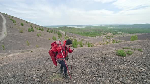 Thumbnail for Female Tourist Climbing Up Rough Trail with Trekking Poles