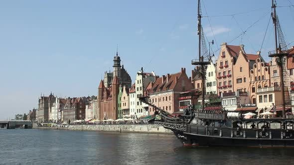 Thumbnail for Stylized tourist sail ship turning on river, ancient historical houses on bank