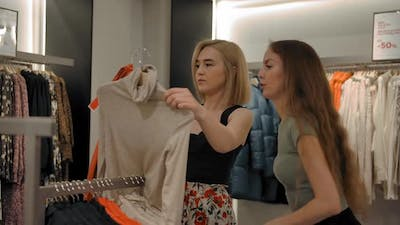 Two Girlfriends Choosing Clothes in a Clothing Store