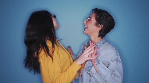 Zwei glückliche, stilvolle Mädchen tanzen und Spaß auf Party haben einzeln auf blauem Hintergrund