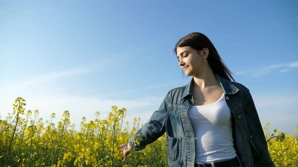 Thumbnail for Beautiful Young Woman Touching the Blossoming Flowers of Rapeseed in Slo-mo