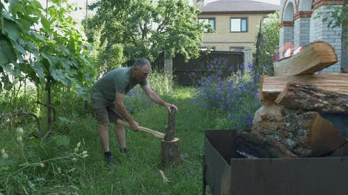 Lumberjack chopping wood with an ax in summer cottage. Logging for grill or BBQ. Men's work
