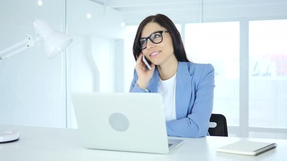 Thumbnail for Young Businesswoman Talking on Phone, Attending Call at Work