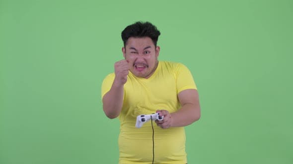 Cover Image for Happy Young Overweight Asian Man Playing Games and Winning