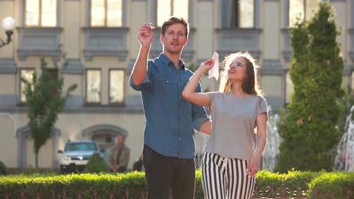 Young Couple Playing with a Paper Aeroplanes Outdoors