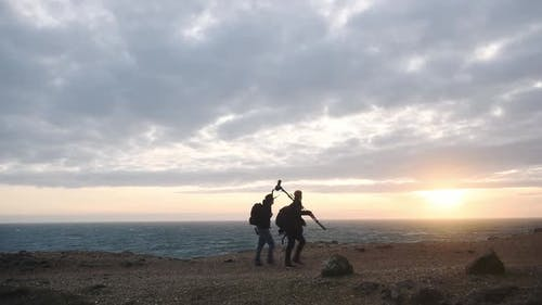 A Couple Of Landscape Photographers takings photos on the Jurassic Coast in Dorset, Carrying Cameras