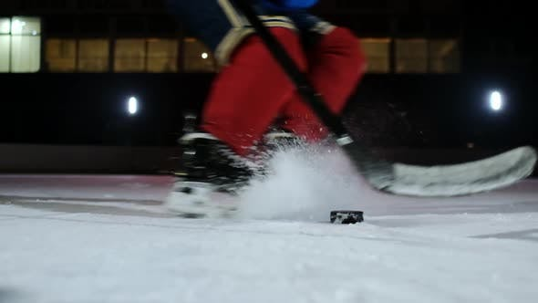 Cover Image for Close-up of the Puck Is on the Ice and in Slow Motion Hockey Player Pulls Up and the Snow Flies Into