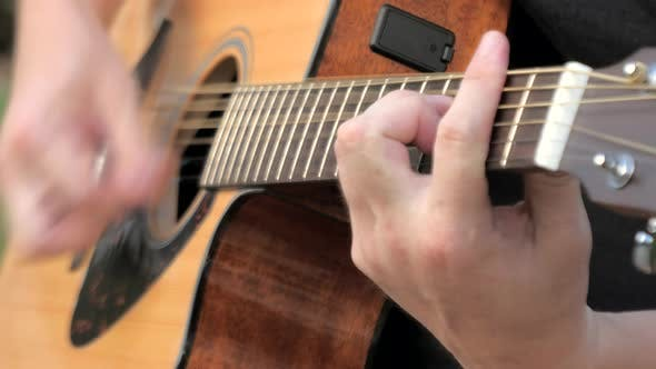 Thumbnail for Close Up of a Young Man Playing Acoustic Guitar Outside. Hands of a Man Playing the Brass Strings of