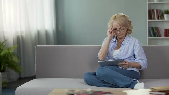 Thumbnail for Adult Woman Sitting on Sofa and Holding Tablet, Buying New Eyeglasses Online
