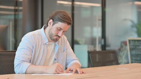 Man Facing Difficulty While Writing on Paper