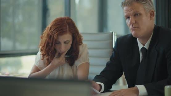 Thumbnail for Mittlere Aufnahme von zwei Personen, die Notizen während eines Geschäftstreffens im Büroraum machen. Zeitlupe