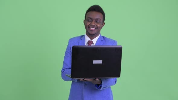 Thumbnail for Happy Young African Businessman Thinking While Using Laptop