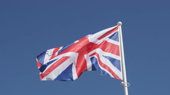 Union Jack national Great Britain symbol waving on flag-pole against blue sky 4K 2160p 30fps UHD foo