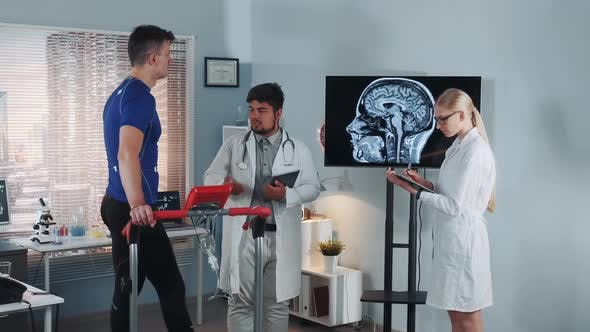 Thumbnail for Multiracial Doctors Speaking About Athlete's Brain MRI on Display