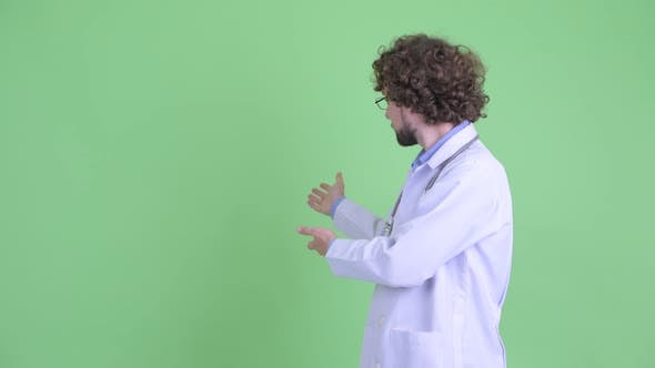 Thumbnail for Happy Young Bearded Man Doctor Showing Something To the Back and Giving Thumbs Up