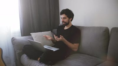 Man Sitting on Sofa and Making a Video Call Gesturing