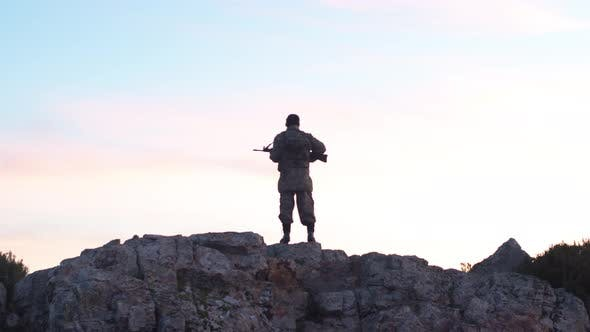 Thumbnail for Soldier In The Morning Holds Guard With His Rifle