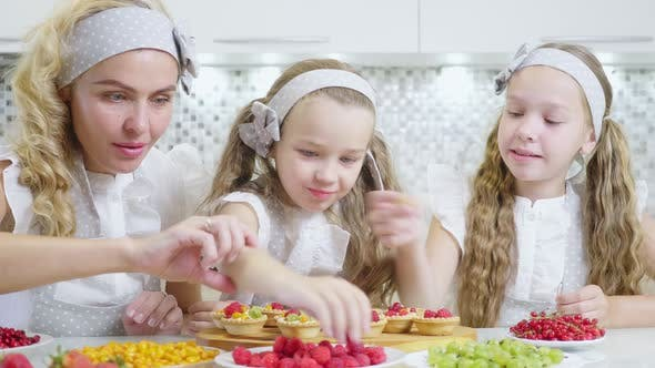 Thumbnail for In the Kitchen Concept. The Family Decorates the Pie and Muffins with a Berry