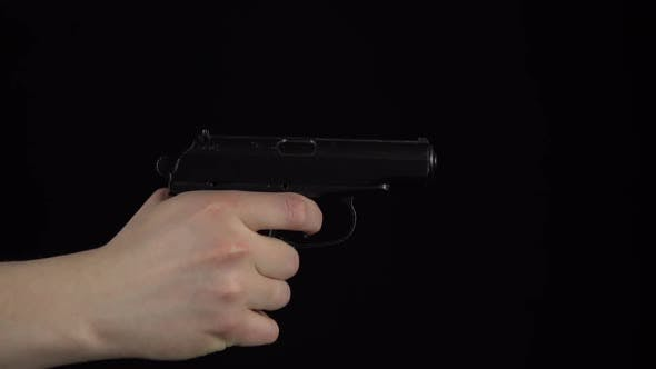 Thumbnail for A Man Makes a Shot From a Pistol. Pistol in Hand Close-up Slow Motion Makes a Shot. On a Black