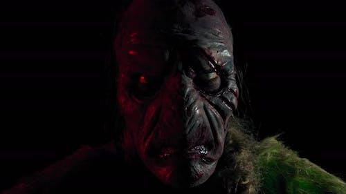 Hässlicher Orc mit dem gruseligen Gesicht starrt in den dunklen Raum, Nahaufnahme,