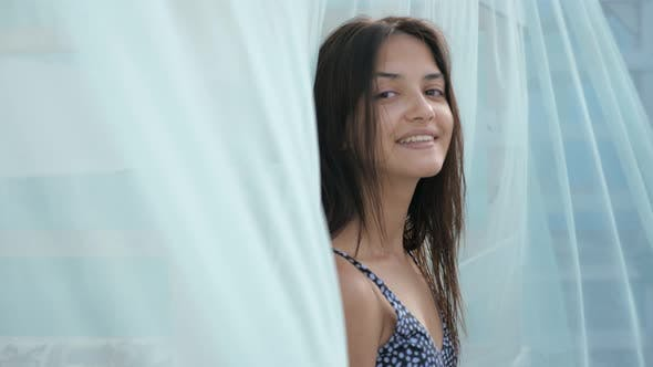 Cover Image for Happy Girl in Bikini Standing, Smiling and Looking Out Up at a Blue Voile in Slo-mo
