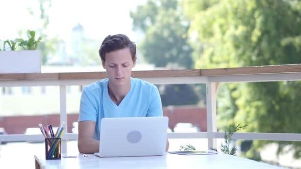 Thumbnail for Junger Mann Arbeiten am Laptop, Sitzen am Schreibtisch, Draussen