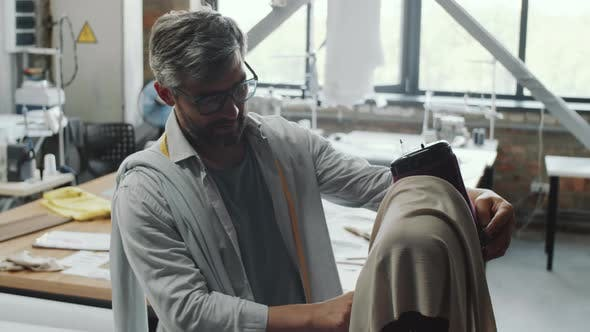 Thumbnail for Male Tailor Putting Fabric on Mannequin while Working in Studio