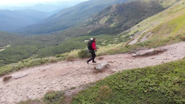 Aerial View of a Traveler Photographer with Backpack Climbing By Mountain Range