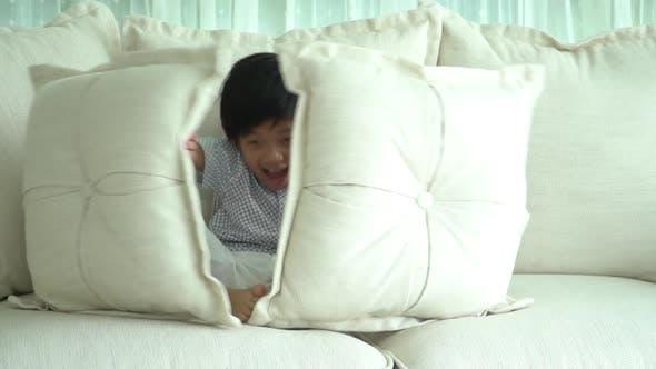 Nettes asiatisches Kind spielt Verstecken auf dem Sofa
