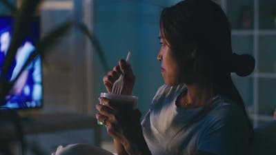 Asian Woman Eating and Watching TV