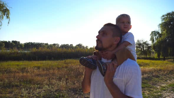 Thumbnail for Happy Family Walking on the Meadow and Relaxing at Nature. Little Boy with Blonde Hair Sitting on