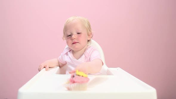 Baby girl sitting in highchair eating cupcake