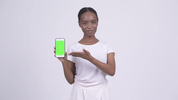 Cover Image for Happy Young Beautiful African Woman Showing Phone and Giving Thumbs Up