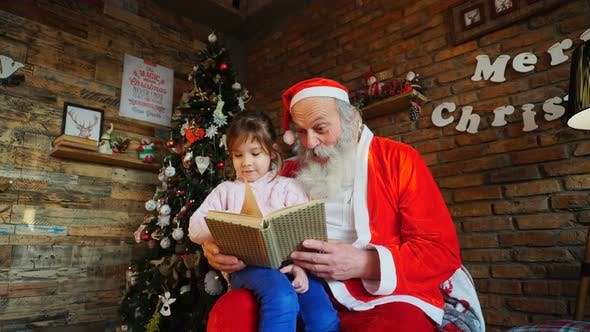 Thumbnail for Santa Claus Sits on Armchair and Reads Book with Fairy Tales for Enthusiastic Little Girl in