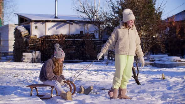 Thumbnail for Funny Girls Playing with Sleigh on Snow at Wintertime