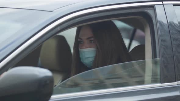 Thumbnail for Side View Portrait of Young Woman in Protective Mask Sitting in Car and Coughing