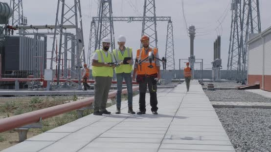 Thumbnail for Employees Using Tablet and Controlling Drone on Power Station