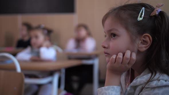 Thumbnail for Focused Schoolgirl Listening To Teacher in Lesson
