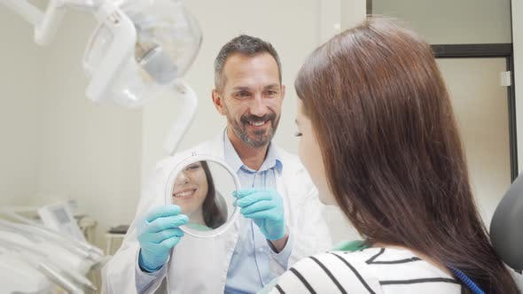 Thumbnail for Cheerful Mature Dentist Holding a Mirror for His Female Patient