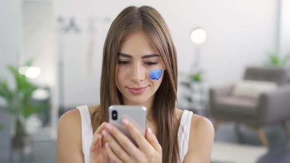 Nahaufnahme Porträt von Junge Angenehme Frau SMS auf Ihr Telefon sitzen zu Hause
