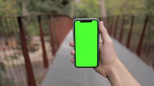 Man watching on iPhone 11 Pro green mock-up blank screen browsing social network in smartphone