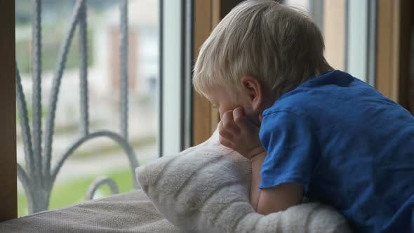 Stay at Home Quarantine Coronavirus Pandemic Prevention, Four Year Old Boy Looks Through the Window