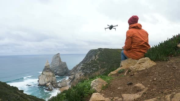 Man Launches Drone Sitting on Rock at Ocean on Cloudy Day